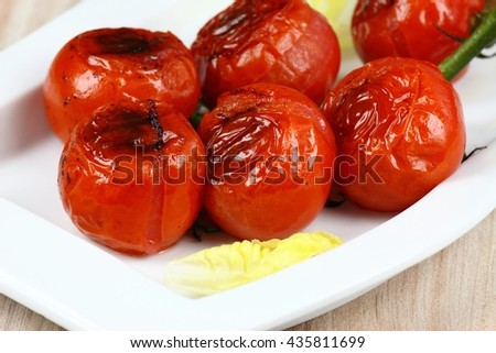 Grilled bunch of tomatoes on the plate ready to eat