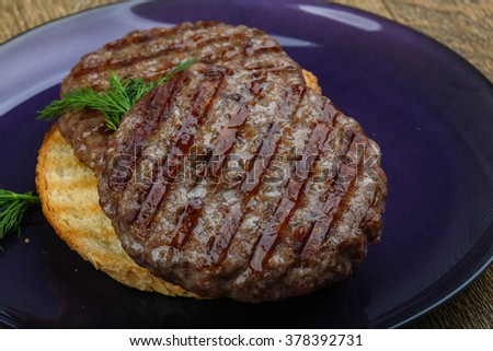Grilled burger cutlet beef minced meat on wood background - stock photo