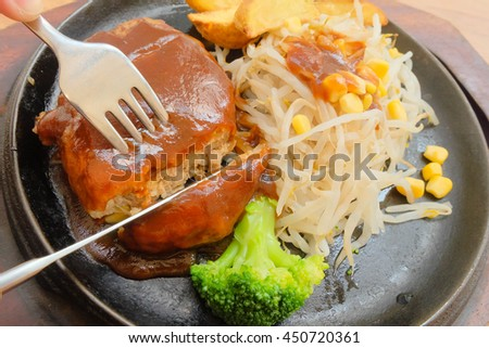 Grilled burger cutlet beef minced meat with fork and knife cutting the beef burger. Served with sided vegetables fried potatoes, bean sprout and broccoli . Selective focus on gravy sauce. - stock photo