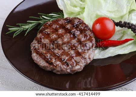 Grilled burger cutlet with rosemary and salad leaves - stock photo
