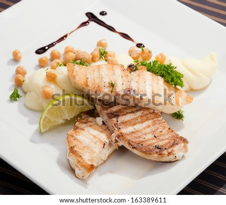 Grilled butter fish  w potato puree peas and lemon - stock photo