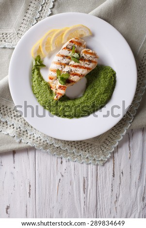 Grilled chicken and a side dish of green peas on a white plate. vertical top view