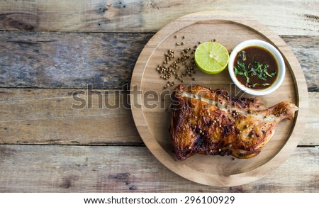 Grilled chicken and lemon on old wooden floor,a particular focus. - stock photo