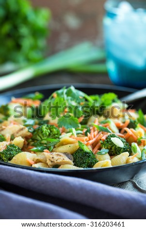 Grilled chicken and shell pasta with fresh vegetables and green onion - stock photo