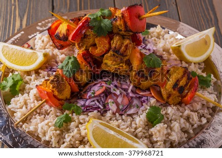 Grilled chicken and vegetable kebabs served with rice and salad on tray. - stock photo
