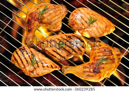 Grilled chicken breast and chicken thigh on the flaming grill - stock photo
