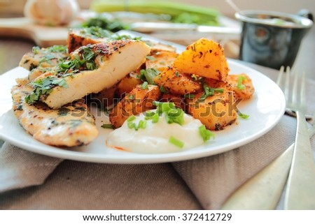Grilled chicken breast fillet in herbs with garlic sauce and fried potatoes - stock photo