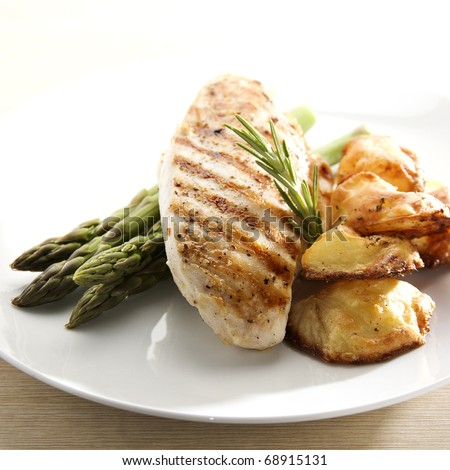 grilled chicken breast fillet with asparagus and roasted potatoes - stock photo