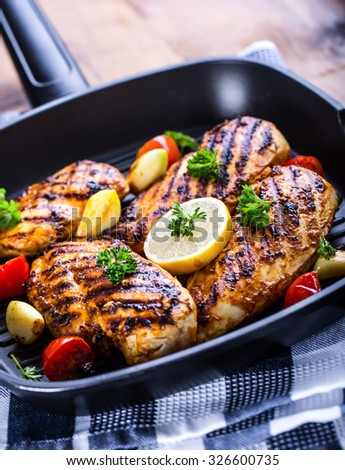 Grilled chicken breast in different variations with cherry tomatoes, green French beans, garlic, herbs, cut lemon on a wooden board or teflon pan. Traditional cuisine. Grill kitchen. - stock photo