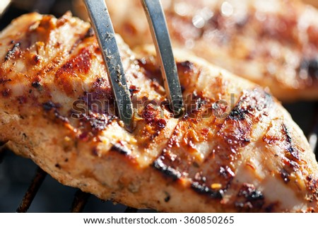Grilled chicken breast on barbeque, cooking process. Macro shot, shallow depth - stock photo