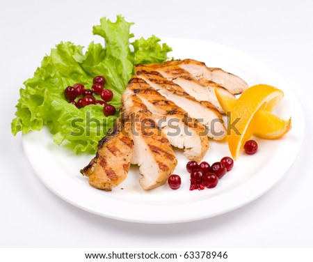 grilled chicken breast, served with cranberries and oranges - stock photo