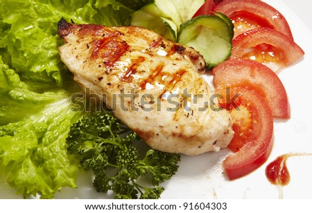 Grilled chicken breast served with lettuce and tomato - stock photo