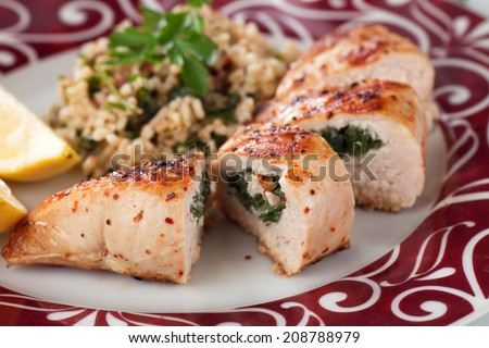 Grilled chicken breast stuffed with spinach, served with bulgur wheat salad - stock photo