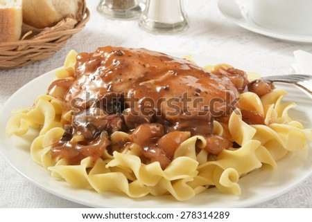 Grilled chicken breast with a mushroom wine sauce on pasta - stock photo