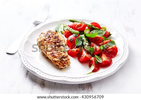 Grilled Chicken Breast with Asparagus and Cherry Tomato Salad with Herbs and Chia Seeds - stock photo