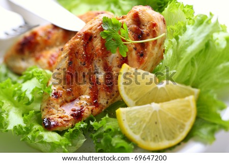 Grilled chicken breast with fresh lettuce and lemon - stock photo