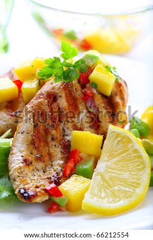 Grilled chicken breast with fresh mango salsa, soft focus - stock photo