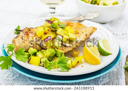 Grilled chicken breast with fresh salsa frompineapple and avocado with red sweet onion , soft selective  focus