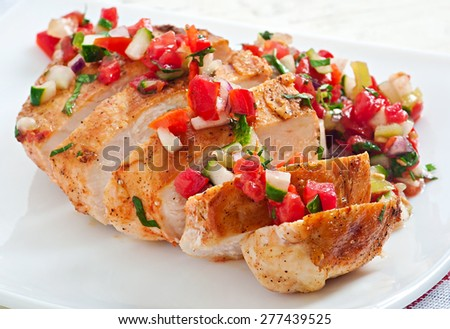 Grilled chicken breast with fresh tomato salsa on white plate - stock photo