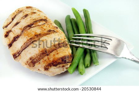 Grilled chicken breast with green beans on a white plate. - stock photo
