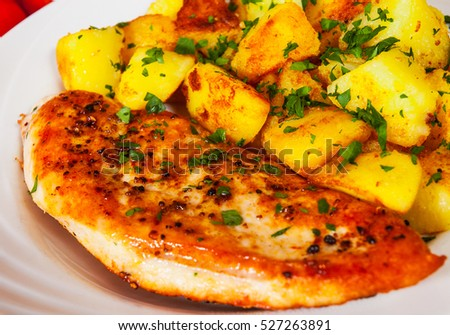 Grilled chicken breast with potato in a plate on wooden table