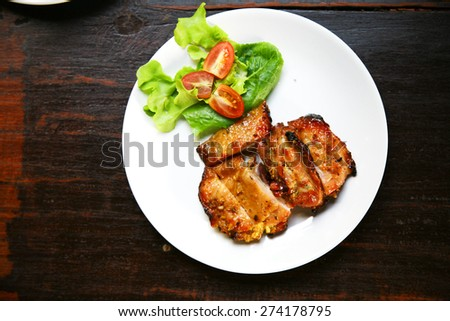 Grilled chicken breast with  salad in white plate  isolated on black table, selective focus - stock photo