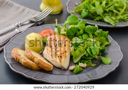 Grilled chicken breast with salad of lamb's lettuce, toasted baguette and dijon mustard - stock photo