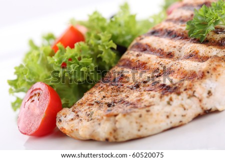 Grilled chicken breasts on a plate with fresh vegetables - stock photo