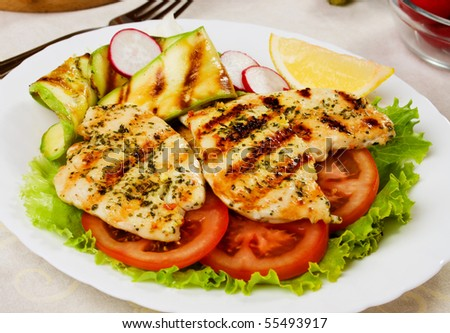 Grilled chicken breasts served with lettuce, tomato and zucchini - stock photo