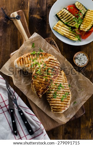 Grilled chicken breasts with grilled vegetables on dark wooden
