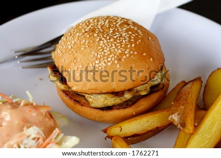 Grilled chicken burger. Served with salad and potato wedge on the side.