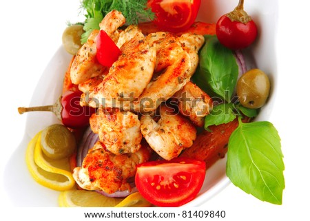 grilled chicken chunks served with tomatoes on white - stock photo