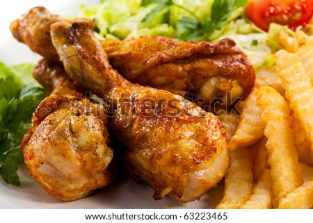 Grilled chicken drumstick, French fries and vegetables - stock photo