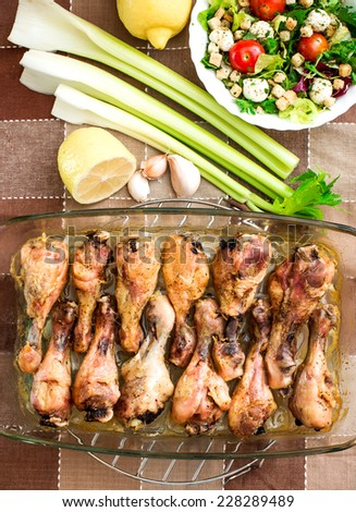 Grilled chicken drumsticks and salad in transparent pot - stock photo