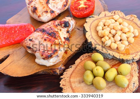 Grilled chicken fillet and and vegetables with olives and chick peas served on a wood - stock photo