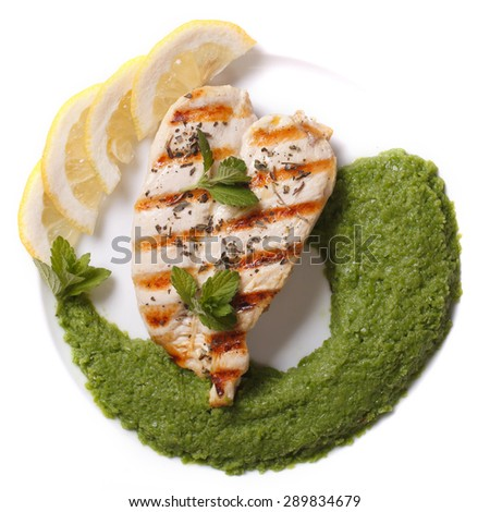 Grilled chicken fillet and mashed peas and mint close-up on a plate. top view - stock photo