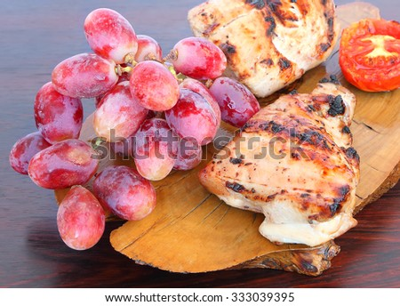 Grilled chicken fillet with vegetables and fruit (red fresh grapes) served on a wood - stock photo