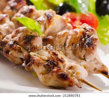 Grilled chicken  kebab  served with fresh salad. Selective focus - stock photo