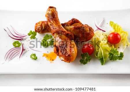 Grilled chicken leg and vegetables on white background - stock photo