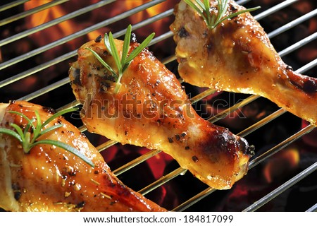 Grilled chicken leg on the flaming grill.