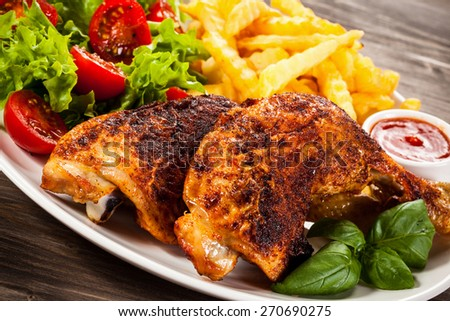 Grilled chicken leg with chips and vegetables