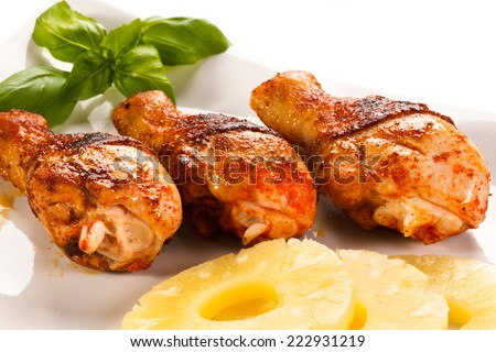 Grilled chicken legs and vegetables on white background - stock photo