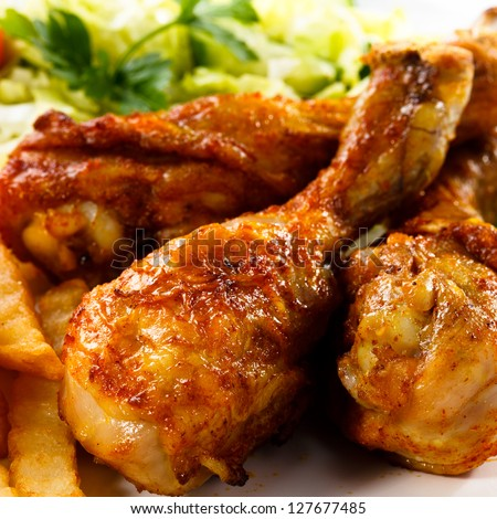 Grilled chicken legs with chips and vegetables - stock photo