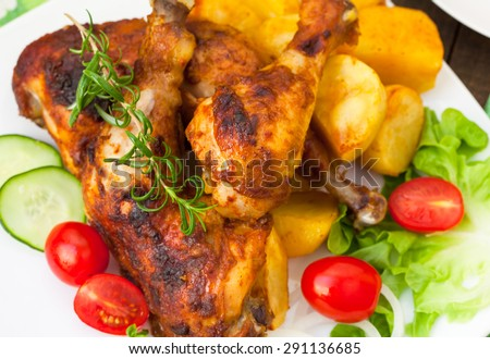 Grilled chicken legs with potatoes and vegetables - stock photo