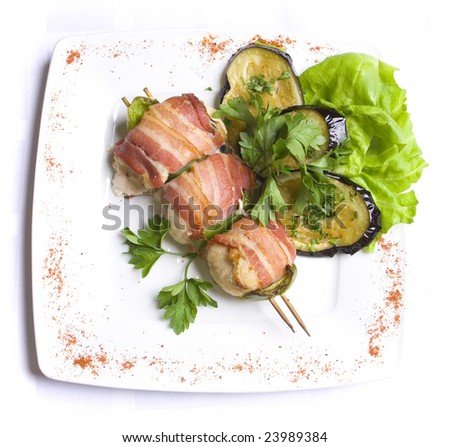 Grilled chiCken meat wraPped in bacon stringed on wooden brochette decorated with grilled egg-plant, leaves of salad and parsley on white plate