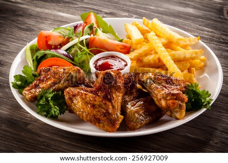 Grilled chicken nuggets, chips and vegetables - stock photo
