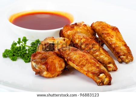 Grilled chicken on a white plate with parsley and sauce in the background.