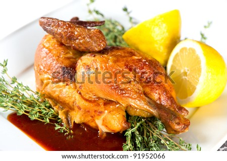 grilled chicken on a white plate with spicy sauce and lemon