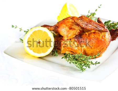 grilled chicken on a white plate with thyme and lemon