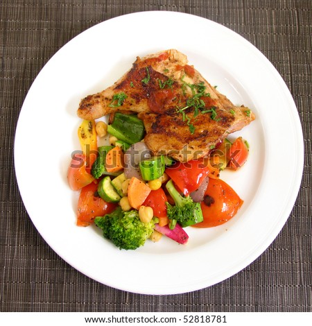 Grilled chicken on a white plate with vegetables on the background. - stock photo